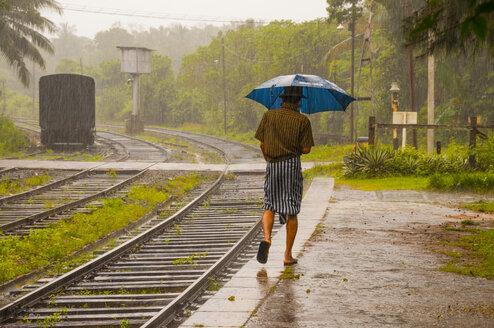 Sri Lanka, Anuradhapura district, Kalawewa, Singhalese walking through monsoon rain at railway station - WG000361