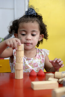 Brazil, Rio de Janeiro, Duque de Caxias, portrait of little girl playing with wooden building bricks in kindergarten - FLK000396