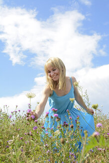 Happy young woman on wildflower meadow picking flowers - BFRF000483