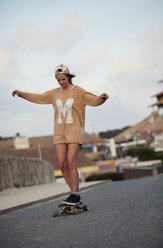 France, Aquitaine, Seignosse, woman longboarding on the street - FAF000030