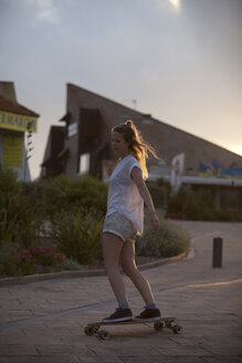 France, Aquitaine, Seignosse, woman longboarding on the street at twilight - FAF000033