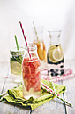 Carafes of miscellaneous fruit infused water on cloth and wood - SBDF001126