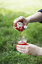 Woman pouring strawberry syrup into glass - EVGF000773