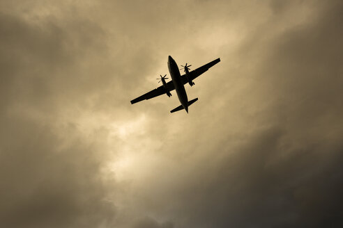 Island, Reykjavik, flying airplane in front of cloudy sky - FC000355