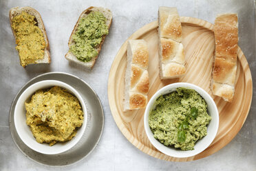 Bowls of pea coriander and carrot fennel hummus and slices of flat bread on wooden board and metal, elevated view - EVG000731