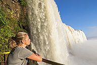 Brazil, Parana, Iguazu National Park, woman standing on view terrace in front of waterfall - FOF006685