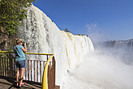 Brazil, Parana, Iguazu National Park, woman photographing waterfalls - FOF006695