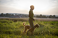 Senior woman walking with her dog over a meadow - FX000053