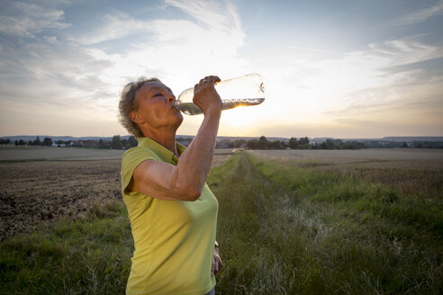 Portrait of senior woman drinking out of water bottle - FX000048