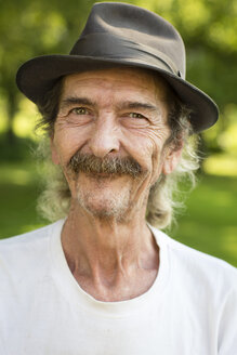 Portrait of smiling senior man with hat and moustache standing in the garden - FX000052