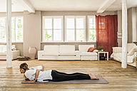Woman practicing yoga in living room - TCF004208