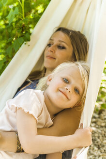 Mother and daughter relaxing in hammock - TCF004163
