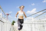 Germany, Munich, Female jogger running on a bridge - MAEF008903