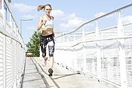 Germany, Munich, Female jogger running on a bridge - MAEF008872
