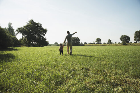 Father walking with his little daughter on a meadow - UUF001522