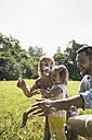 Parents and little daughter making soap bubbles on a meadow - UUF001527