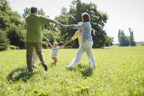 Three generations family playing ring-a-ring-a-roses on a meadow - UUF001539