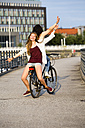Germany, Berlin, two female friends driving on a bicycle - FX000057