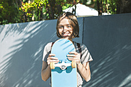 Portrait of smiling young female skate boarder holding her skateboard - EBSF000272