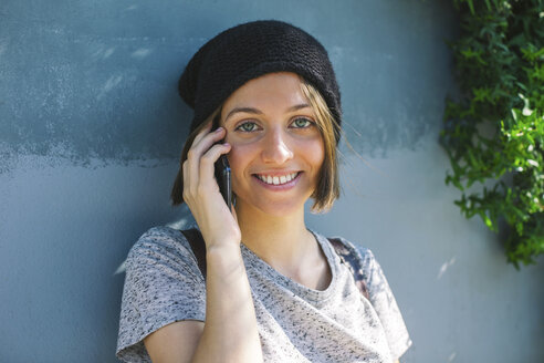 Portrait of smiling young female skate boarder telephoning with smartphone - EBSF000276