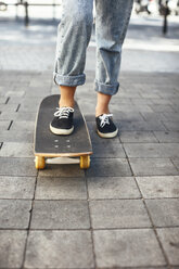 Young female skate boarder on her skateboard, partial view - EBSF000287