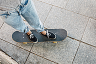Young female skate boarder standing on her skateboard, partial view - EBSF000291