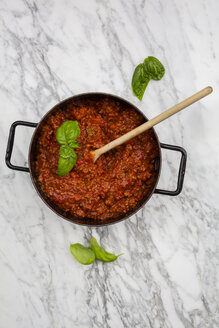 Cooking pot of Bolognese sauce and basil leaves on white marble, elevated view - LVF001740