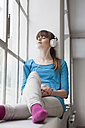 Portrait of young woman sitting on window sill in an office listening music with headphones - RBF001690