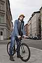 Germany, Bavaria, Munich, young man wearing basecap standing on pavement with his racing cycle - RBF001701