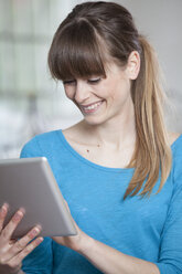 Portrait of smiling young woman in an office using tablet computer - RBF001722