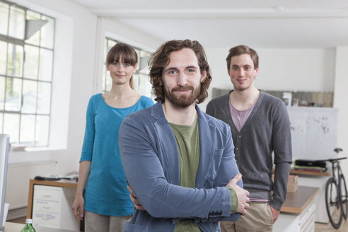 Portrait of young man with his two colleagues in the background standing in a creative office - RBF001741