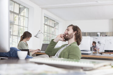 Young man telephoning at his desk in a creative office - RBF001764