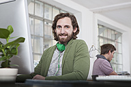 Portrait of smiling young man sitting at his desk in a creative office - RBF001767