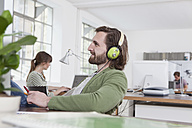 Young man sitting at his desk in a creative office hearing music with headphones - RBF001784