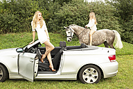 Young woman standing in a cabriolet while teenage girl riding on a horse in the background - FC000375