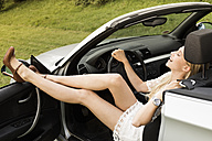 Laughing young woman sitting in cabriolet with feet up - FC000377