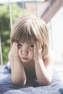 Portrait of sad little girl lying on towel on balcony - LVF001746