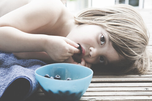 Little girl eating blueberries on balcony - LVF001750