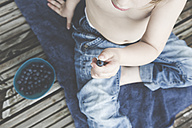 Little girl with bowl of blueberries on balcony, partial view - LVF001752