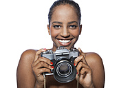 Portrait of smiling woman holding camera in front of white background - KDF000481
