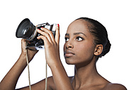 Portrait of woman holding camera in front of white background - KDF000483
