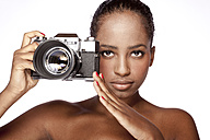 Portrait of woman holding camera in front of white background - KDF000489