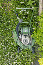 Old green lawn mower standing on savaged meadow, elevated view - BSC000437