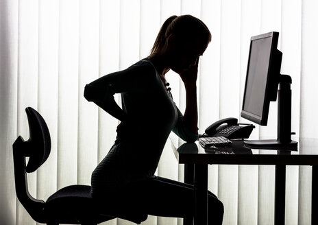Silhouette of woman at desk having back pain - EJWF000456