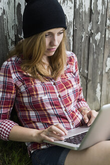 Portrait of a young woman with laptop in front of a wooden wall - SEF000830