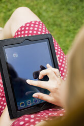 Young woman sitting in a garden chair touching display of digital tablet, partial view - SE000834
