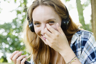 Portrait of a smiling young woman with headphones - SEF000822