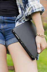 Young woman holding digital tablet in her hand, partial view - SEF000824