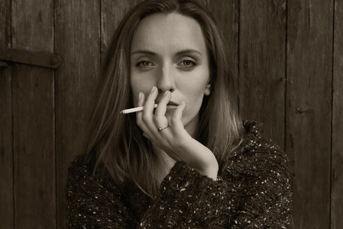 Portrait of a smoking young woman in front of a wooden door - SE000828