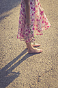 Girl standing barefoot on road holding flower - SARF000752